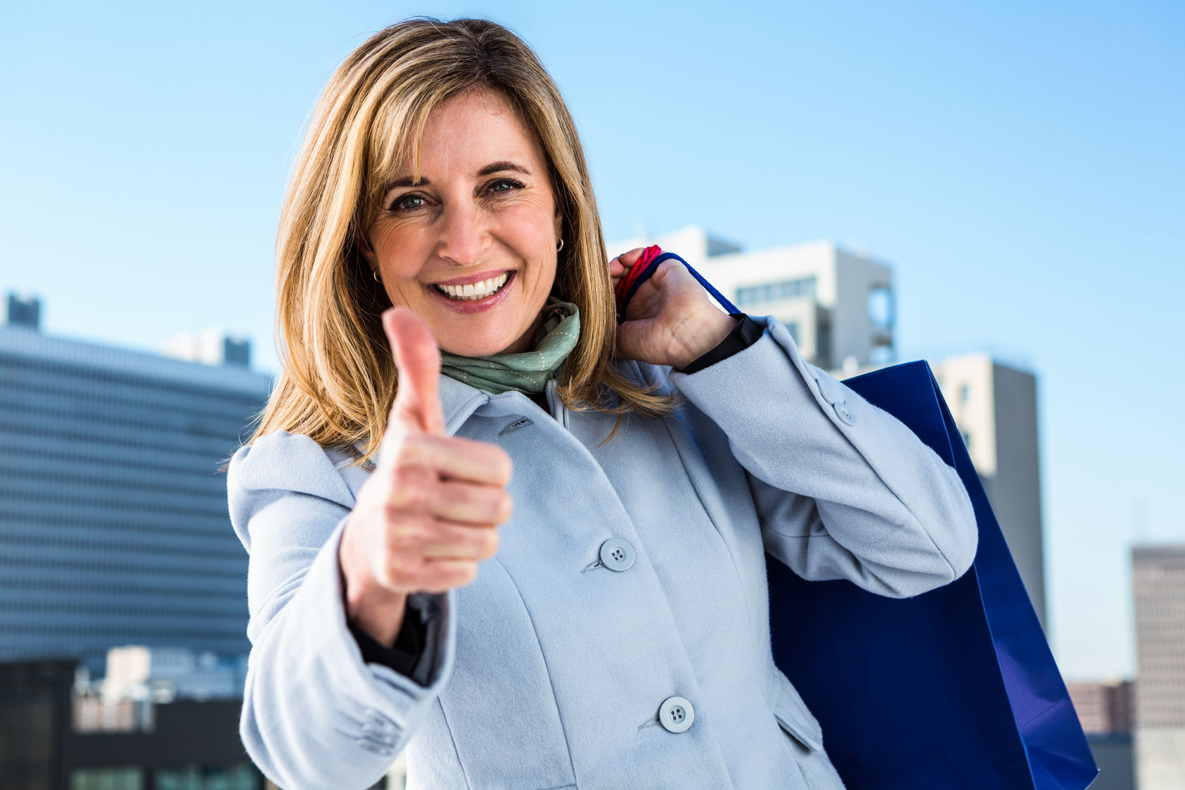 51330935 - woman doing a thumbs up during her shopping in town